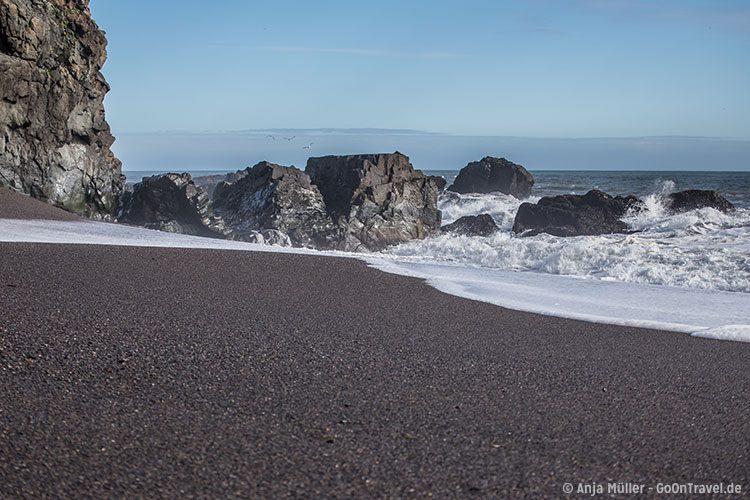 Feinkörniger schwarzer Sand am Strand