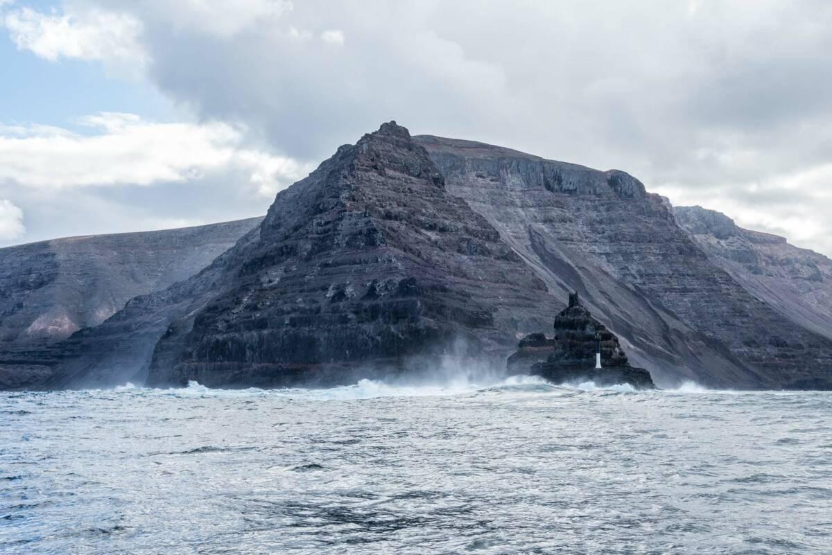 Die beeindruckende Gebirgskette Risco de Famara und Punta Fariones mit Leuchtturm